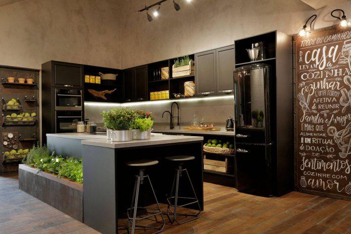 uma cozinha muito bonita e especial apesar do piso e parede não serem os tradicionais do estilo, veja que é possível ver claramente a presença do industrial nos detalhes como: na iluminação nos móveis e enfeites