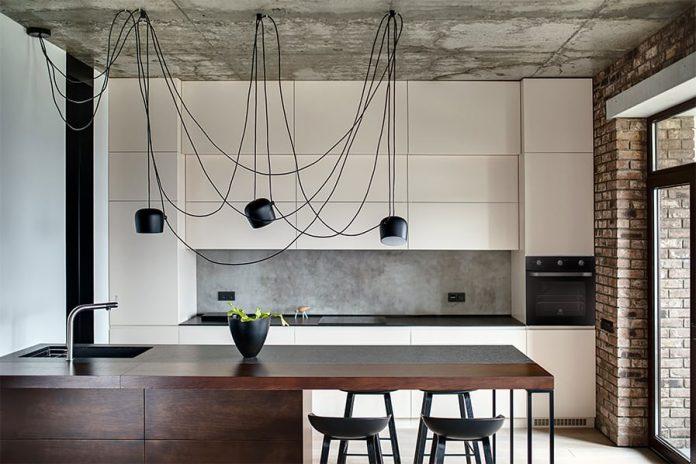 Aqui uma cozinha muito bem decorada onde o teto sem revestimento com a iluminação feita por pendentes cheios de fios, a parede em tijolinho, trouxeram muito charme e beleza ao local.