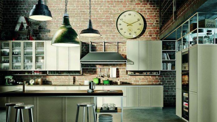 uma cozinha bem típica do estilo parede em tijolinho, chão de cimento queimado, iluminação com fios aparentes utilizou uma ilha com bancos