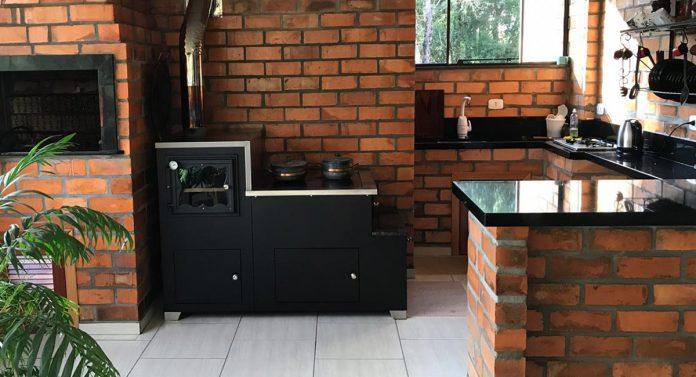 fogão a lenha comprado feito em ferro que trouxe muita beleza a cozinha e deu um contraste pelo fato da cozinha ser toda de tijolinho